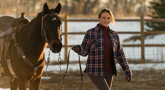 Mädchen führt Pferd an Zügeln