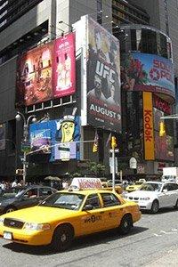 gelbes Taxi auf den Straßen New Yorks, im Hintergrund erkennt man Poster