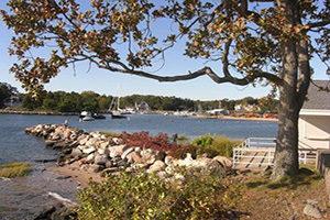Ein Hafen im Hintergrund, im Vordergrund eine Steinmauer und ein Baum