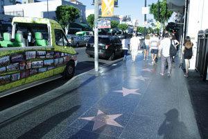 Straße mit Sternen (walk of fame) rechts Straße mit Sternen (walk of fame) rechts sind einige Leute, links ein buntes Auto