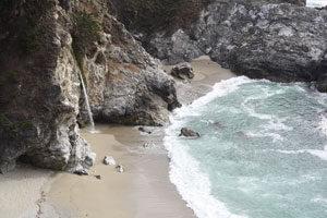 Wasserfall kommt aus einem Felsen, daneben ist das offene Meer