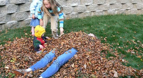 Sandra spielt mit drei Kindern im Laub.