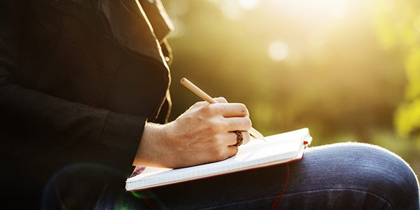 Eine Frau schreibt Notizen in ein Buch