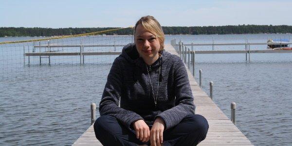 Maike sitzt im Schneidersitz auf einem Steg, im Hitergrund sieht man den See des Camps