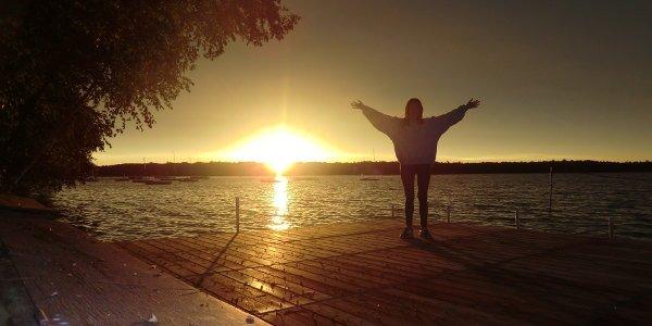 See bei Sonnenuntergang, mit Silhuette einer Frau