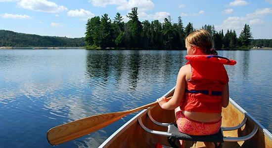 Junge Frau im Kanu auf einem See