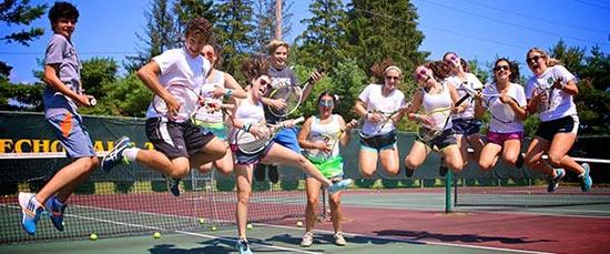 Jugendliche Tennisspieler springen freudig in die Luft.