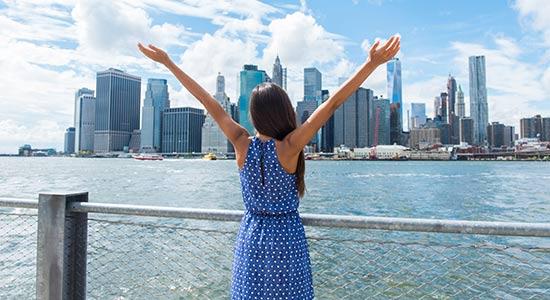 junge Frau steht vor der Skyline von Manhattan (USA)
