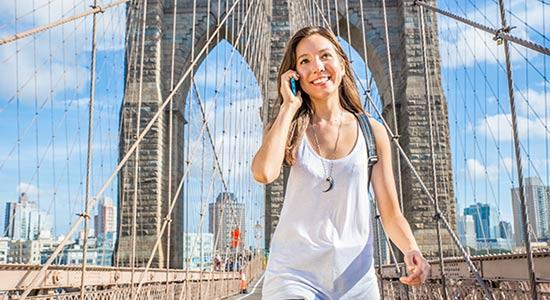 junge Frau läuft über die Brooklyn Bridge in Manhattan (USA)